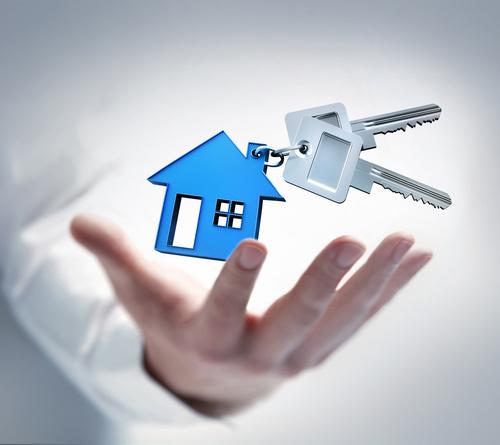 Hand mit Schlsseln und blauem Haus