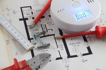 CO Melder auf einem Bauplan mit Werkzeug
