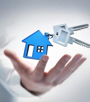 Hand mit Schlüsseln und blauem Haus